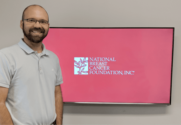 Justin standing in front of NBCF logo